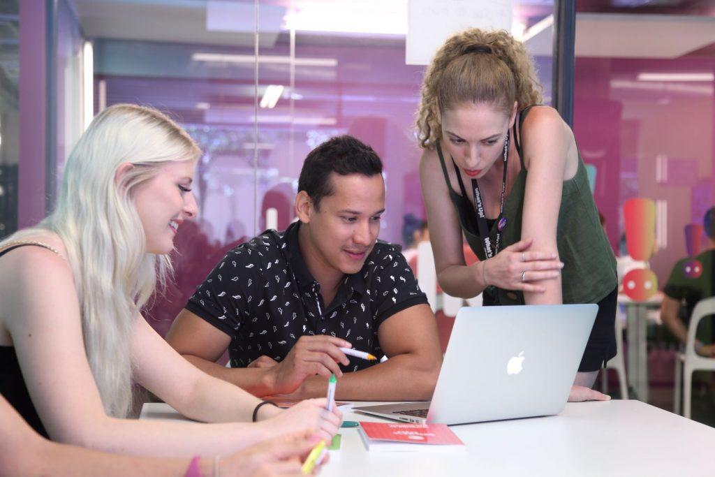 Estudiantes de inglés en una de las academias What's Up! revisando el contenido de su lección junto a una profesora